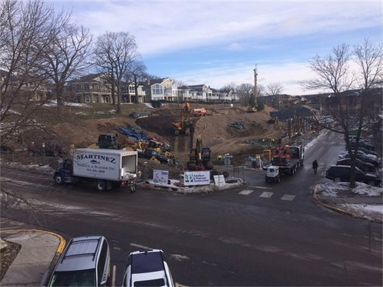 In the center of the photo, the backhoe and crane are preparing for retaining wall construction.   To the right of the photo, columns are starting to rise from the site along the south edge of the ramp. Photo Credit: Kevin Klapprich