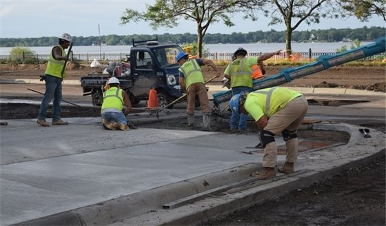Crews pouring cement for a sidewalk and curbs at Lake Street and Walker Ave.