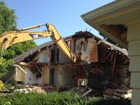 A bulldozer demolishing a house
