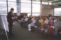 A police officer giving a demonstration to a group of citizens