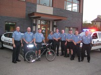 The reserve unit standing in front of the police station and cruisers